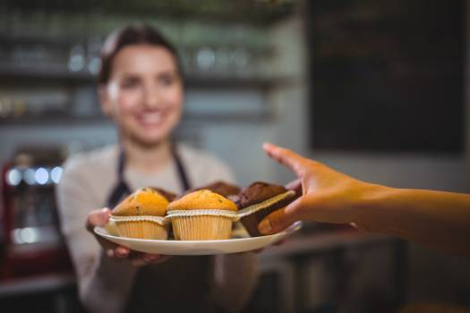 Waitress serving a plate of cupcake to customer #410110
