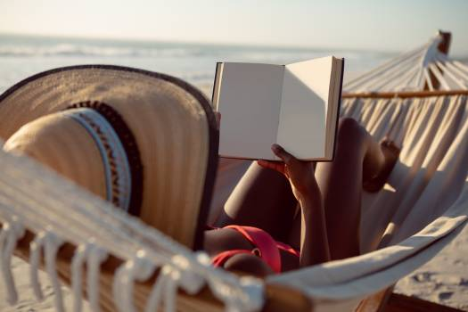 Woman reading a book while relaxing in hammock on the beach #410121