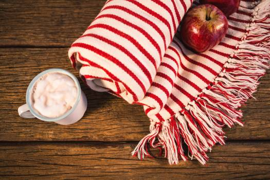 Rolled blanket with two apples and coffee mug #410131