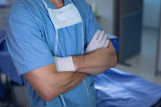 Male surgeon standing with arms crossed in operating room at hospital #410164