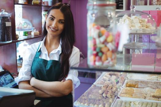 Portrait of female shopkeeper standing at turkish sweets counter #410170