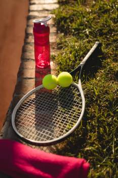 Water bottle, tennis ball, racket and napkin on grass #410186