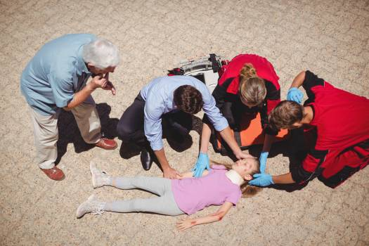 Paramedics examining injured girl #410189