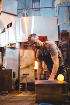 Glassblower shaping a molten glass #410208
