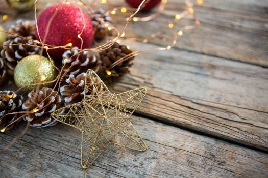 Close-up of star, rice lights, bauble ball and pine cone on wooden plank #410211