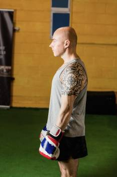 Boxer standing with boxing gloves in fitness studio Free Photo