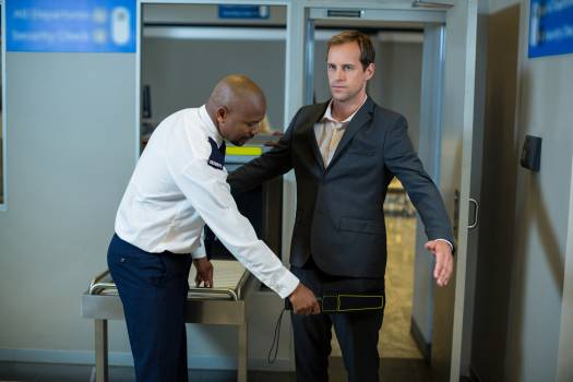 Airport security officer using a hand held metal detector to check a commuter #410345