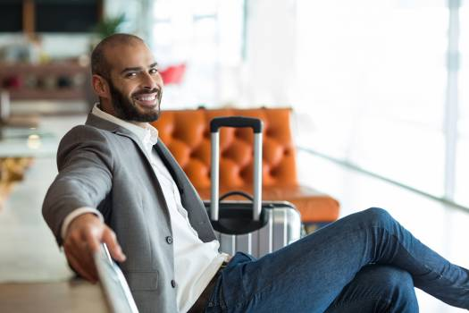 Portrait of smiling businessman sitting on chair in waiting area Free Photo