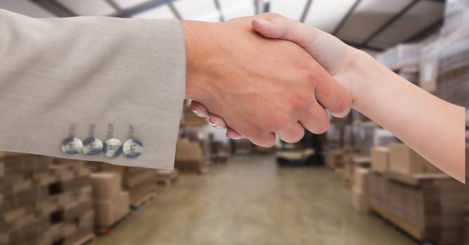 Close-up of business people shaking hands in warehouse #410377