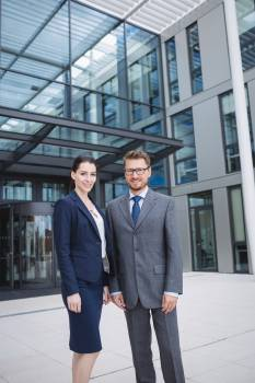 Confident businessman with colleague standing outside office building Free Photo