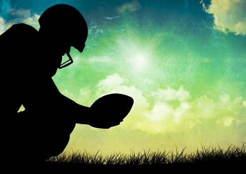 Silhouette of player holding rugby ball against sky in background #410393