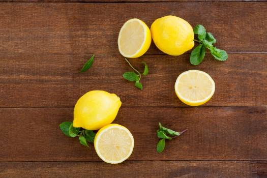 Full and half lemons and mint leaves on table #410407