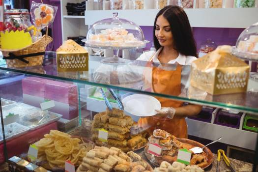 Female shopkeeper serving turkish pastries in a plate at counter #410415