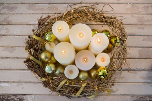 Candles and bauble ball in nest basket on wooden plank #410419