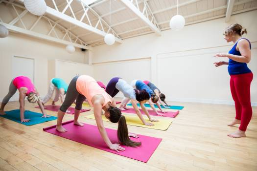 Trainer assisting group of people with downward dog yoga exercise #410421