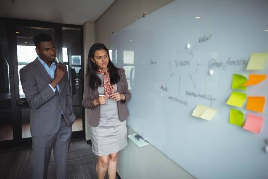 Businessman and a colleague looking at white board in conference room Free Photo