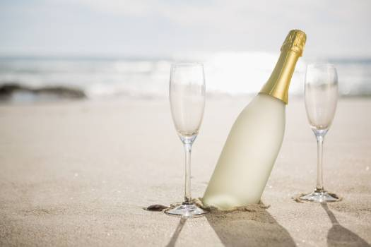 Champagne bottle and two glasses on sand #410494