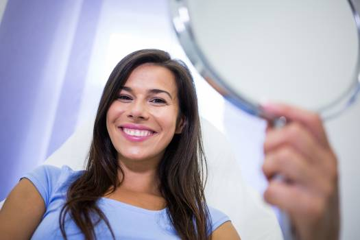 Smiling patient holding a mirror at clinic #410556