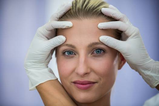Doctor examining female patients face from cosmetic treatment Free Photo