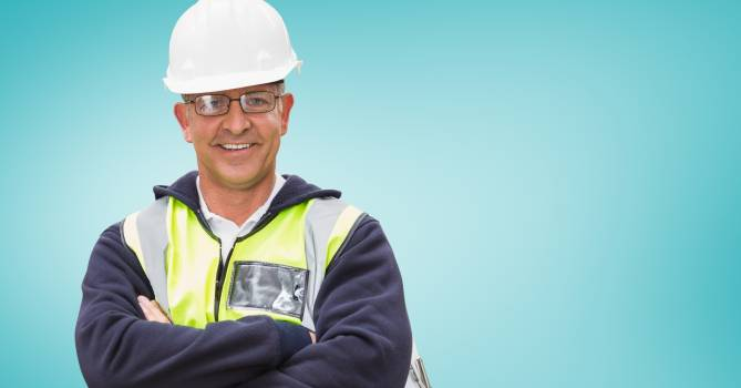 Architect in hardhat and spectacles standing with arms crossed against blue background #410580