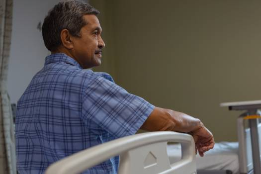 Mature male patient sitting on medical bed and looking away in medical ward at hospital #410608