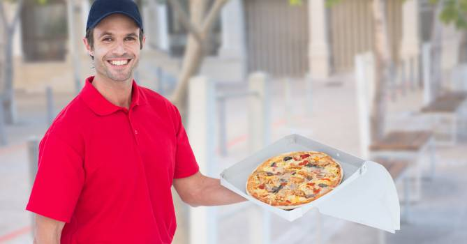 Happy delivery man holding pizza box Free Photo