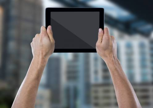 Hand with tablet against blurry building #410637