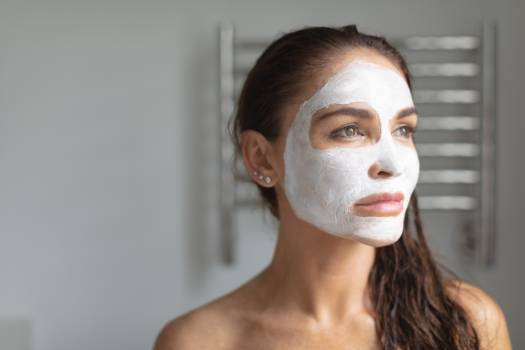 Woman with facial mask standing in bathroom at home #410668