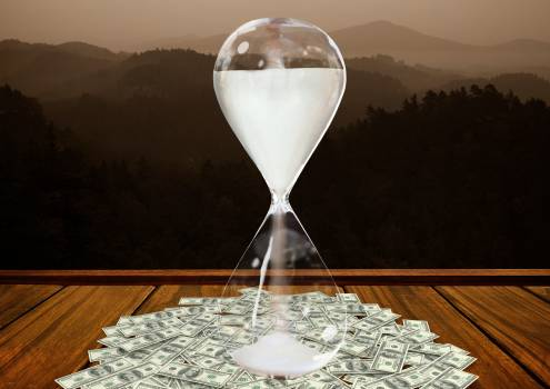Currency flowing through hour glass on wooden plank against mountains in background #410694