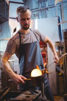 Glassblower forming and shaping a molten glass Free Photo