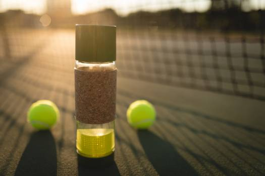 Close-up of tennis ball and water bottle in ground #410734