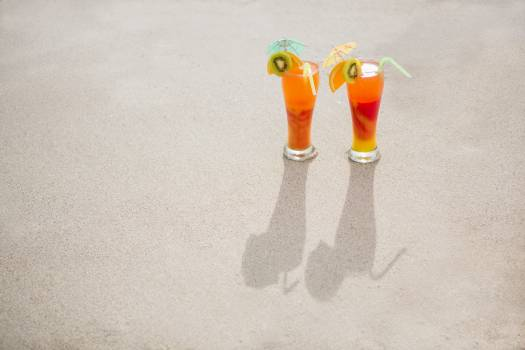 Overhead view of two glasses of cocktail drink kept on sand #410744