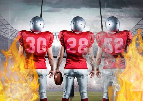 American football players standing with ball against flames and stadium in background Free Photo