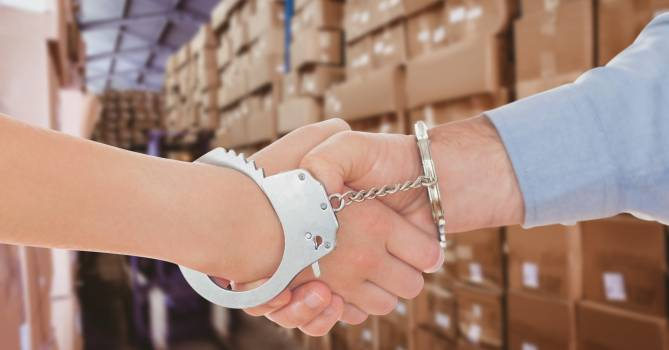 Digital composite image of business people in handcuffs shaking hands in warehouse #410781