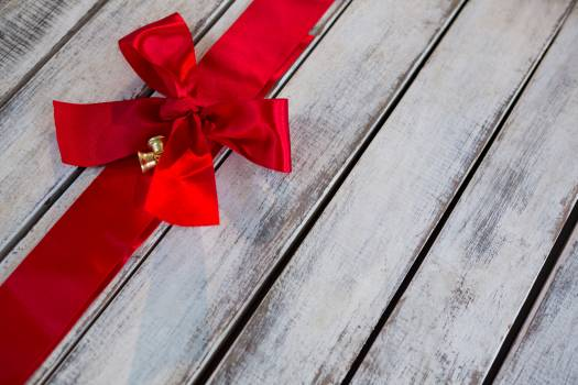 Red ribbon tied on wooden plank #410783