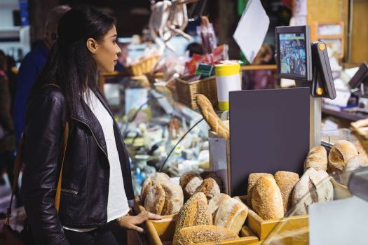 Woman standing at bread counter Free Photo
