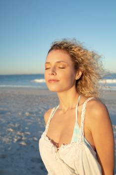 Woman standing with eyes closed on the beach #410785