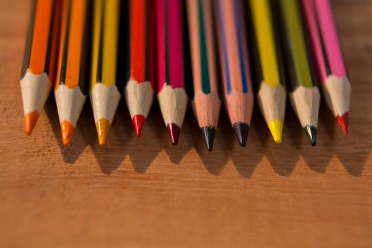 Various color pencils on wooden table Free Photo