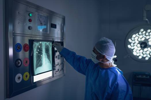 Male surgeon examining x-ray report on x-ray light box in operation theater #410804