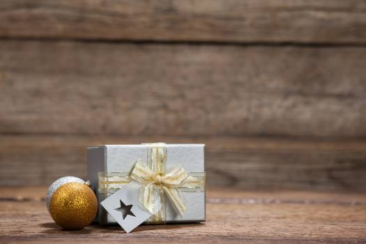 Wrapped gift box and baubles on wooden table #410829