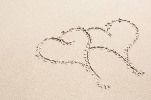 Two heart shapes drawn on sand #410890