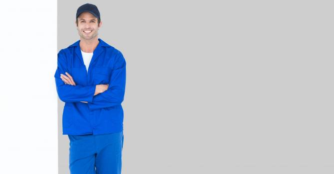 Worker standing arms crossed by bill board #410923
