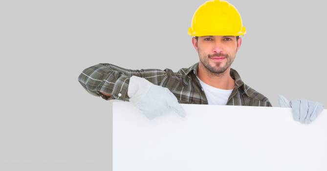 Worker wearing hardhat while pointing at blank bill board #410936