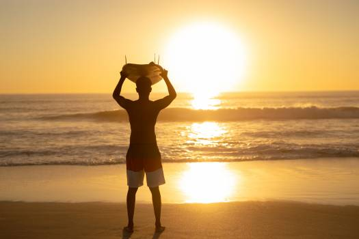 Man carrying surfboard on his head at beach #410962