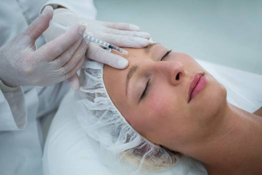 Female patient receiving a botox injection on forehead Free Photo