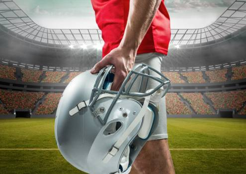 Mid section of an American football player holding helmet in stadium #410984