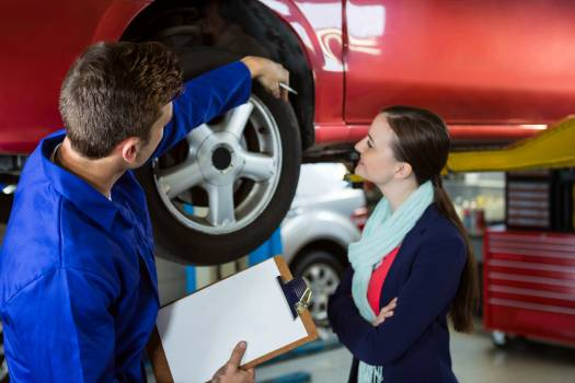 Mechanic showing customer the problem with car #410989