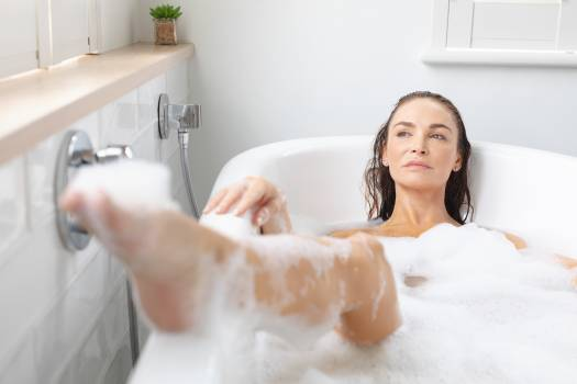 Woman taking bubble bath in bathroom at home #410996