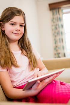 Girl sitting on sofa using digital tablet in living room Free Photo