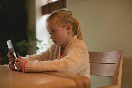 Cute girl using digital tablet in living room Free Photo